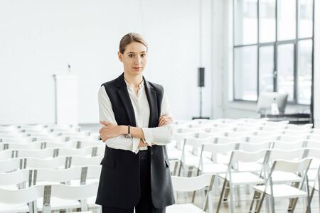 attractive woman in formal wear with crossed arms in conference hall
