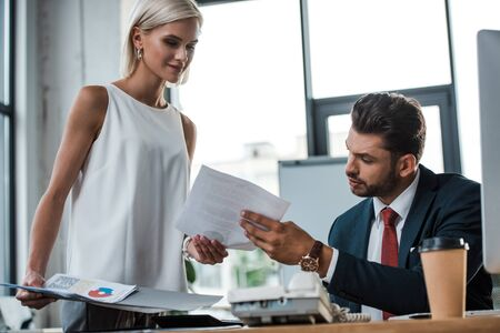 selective focus of happy blonde woman holding folder near businessman in office