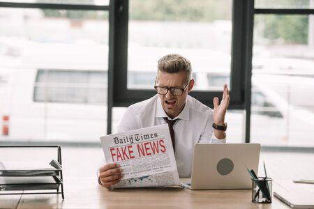 upset businessman in glasses gesturing while reading newspaper with fake news
