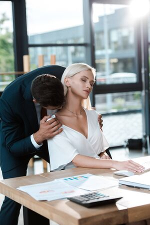 selective focus of man standing and flirting near blonde young woman with closed eyes