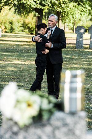 selective focus of senior man hugging upset woman in cemetery
