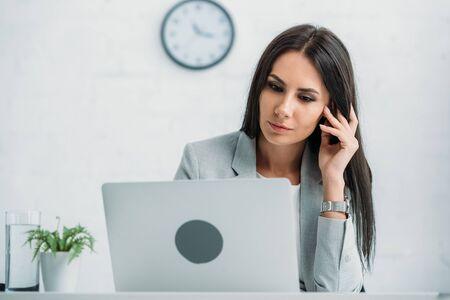 beautiful and brunette woman in formal wear using laptop Фото со стока