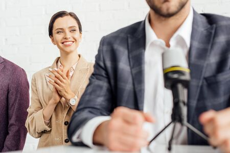 selective focus of attractive businesswoman in formal wear clapping in conference hall