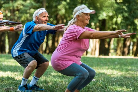 happy multicultural retired people doing sit ups on grass Foto de archivo - 130219384