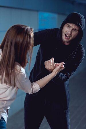Mujer defendiéndose de atacar a un ladrón en una sudadera con capucha negra en el paso subterráneo Foto de archivo