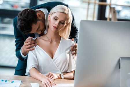 selective focus of bearded businessman flirting with woman sitting near table
