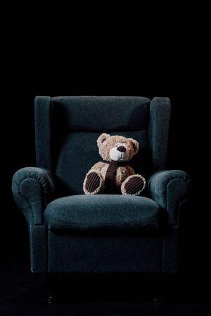 gray soft armchair with plush teddy bear isolated on black