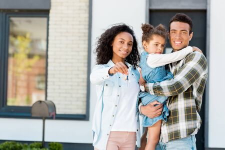 family standing near new house and looking at camera while father holding kid and mother showing key to camera