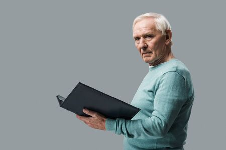 upset retired man with grey hair holding photo album isolated on grey