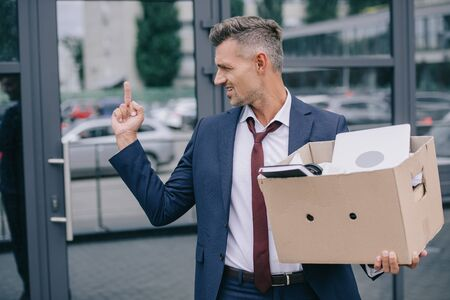 upset man in suit showing middle finger while holding box near building