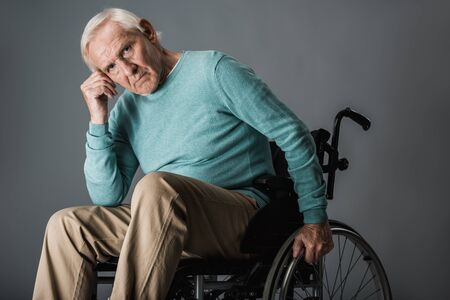 upset retired man sitting in wheelchair and looking at camera on grey Reklamní fotografie