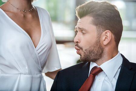 El enfoque selectivo del hombre sorprendido mirando a la mujer en la oficina