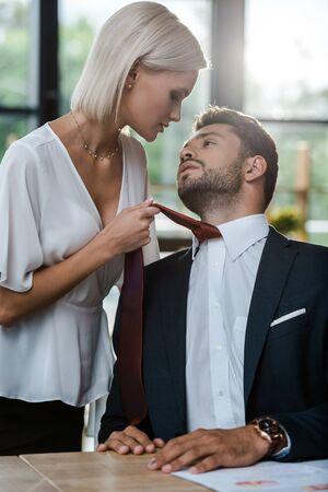 namiętna kobieta dotykająca krawata przystojnego mężczyzny podczas flirtowania w biurze
