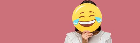 panoramic shot of woman covering face with smiley isolated on pink