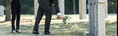 panoramic shot of man putting flowers near tombstones and woman