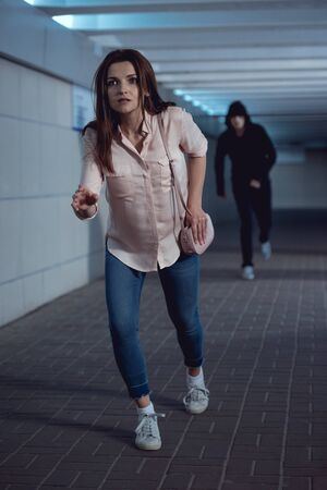 frightened woman running away from thief in underpass