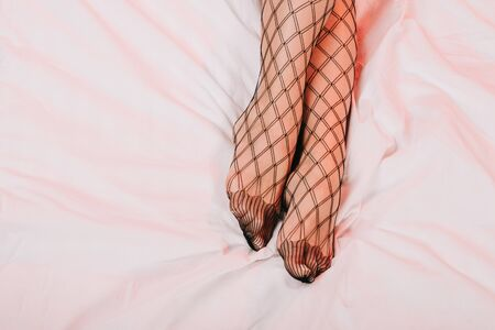 cropped view of woman in mesh stockings on while bedding Stock fotó