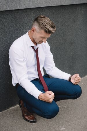 upset businessman sitting with clenched fists outside