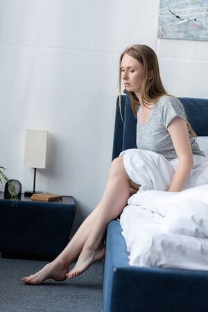 tired barefoot woman sitting on bed in bedroom