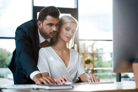 Selektiver Fokus eines bärtigen Geschäftsmannes im Anzug, der in der Nähe eines attraktiven blonden Mädchens im Büro steht Standard-Bild