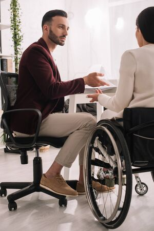 back view of disabled businesswoman gesturing while talking to business partner in office Imagens