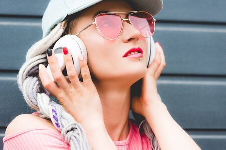 beautiful stylish girl with dreadlocks in sunglasses with hands on headphones