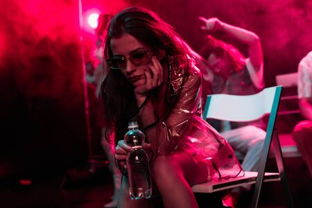 sick young woman sitting with bottle of water in nightclub