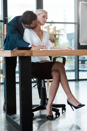 bearded businessman kissing neck of attractive blonde woman with closed eyes