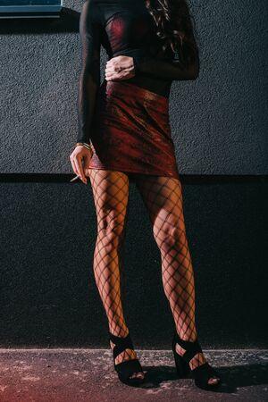 Ausgeschnittene Ansicht einer Frau im roten Rock, die in der Nähe der Wand steht und eine Zigarette hält