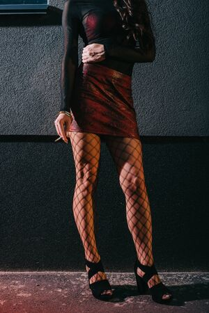 cropped view of sexy woman in red skirt standing near wall and holding cigarette