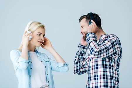 man and girl in headphones looking at each other isolated on grey