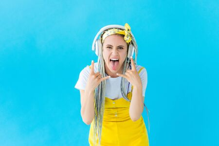 girl with dreadlocks in headphones sticking out tongue and doing rock signs isolated on turquoise Banco de Imagens