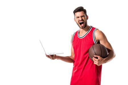 Gritando jugador de baloncesto con pelota usando laptop aislado en blanco Foto de archivo