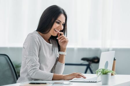 beautiful and brunette woman smiling and looking at screen of laptop