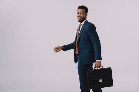 happy african american man in suit holding briefcase isolated on grey