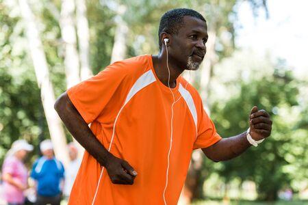 selective focus of senior african american man running and listening music in earphones
