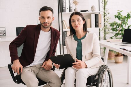 positive disabled businesswoman holding clipboard while sitting near business partner in office