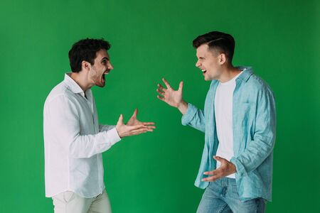 two men in shirts quarreling and screaming at each other isolated on green