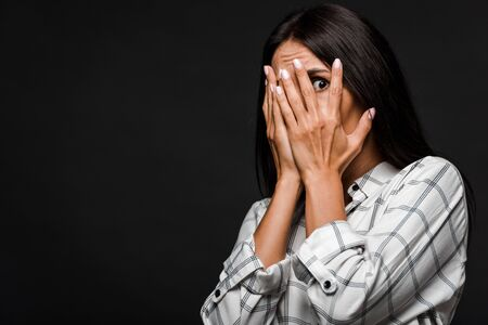 scared woman covering face isolated on black