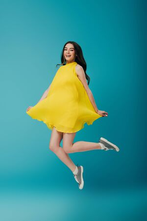 full length view of happy girl in yellow dress jumping on turquoise background