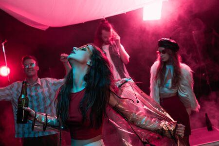 chica sosteniendo cerveza y bailando en la discoteca con humo rosa