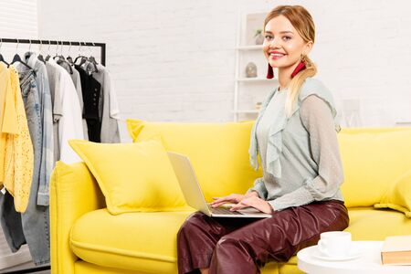 smiling freelancer sitting on yellow sofa and using laptop at home Stockfoto