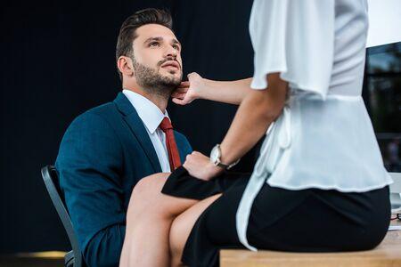mise au point sélective d'un bel homme regardant une femme en train de flirter assis sur une table