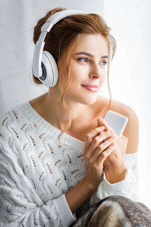 attractive woman in white sweater listening music and holding smartphone
