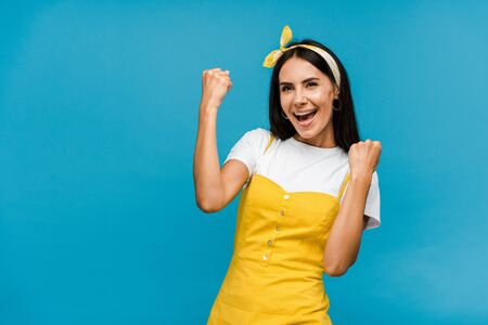 excited woman in headband gesturing isolated on blue