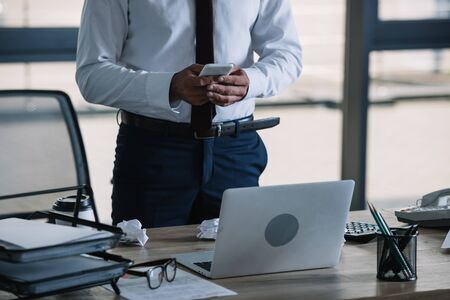 cropped view of businessman using smartphone near laptop in office