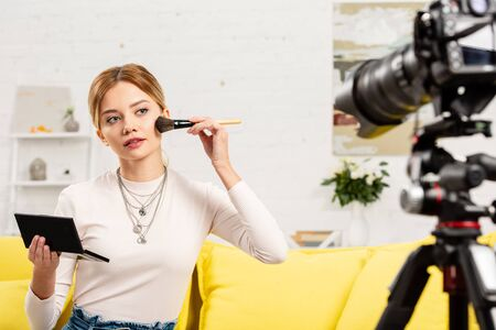beauty blogger sitting on yellow sofa and doing makeup in front of video camera