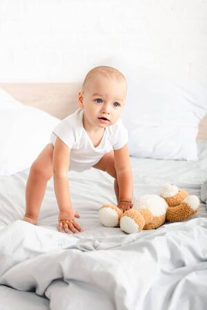 Cute child in white clothes grubbing his teddy bear from the bed Stock Photo