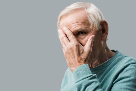 upset retired man covering face and looking at camera isolated on grey
