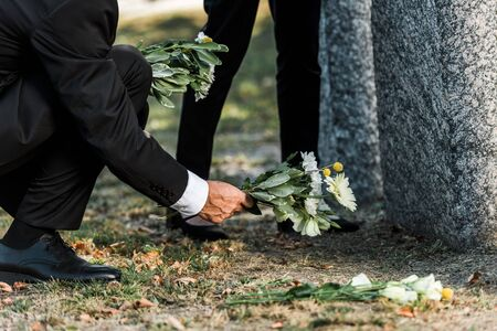 cropped view of senior man putting flowers near tombstones and woman